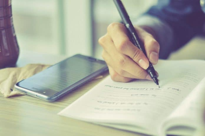 taking notes with notebook and phone